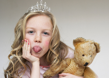 Blond little girl holding a teddy and poking her tounge out