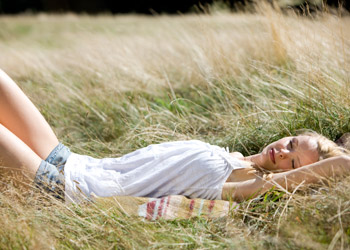 Blond Woman lying sleeping on a field by summer in nature