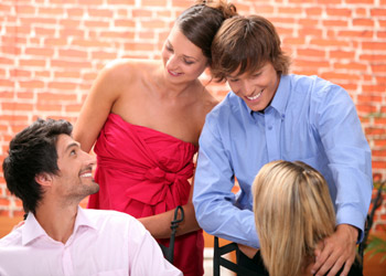 Group of smiling adults meeting each other with red wall in the background