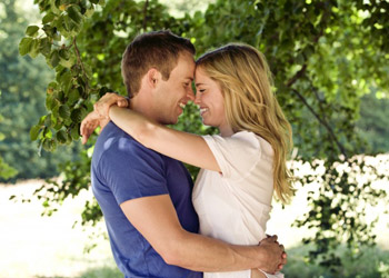 Young smiling couple hugging in front of a big tree in nature