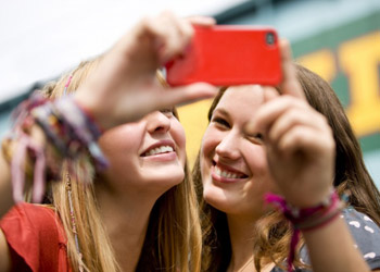 Smiling teenage girls taking selfies with a red smartphone