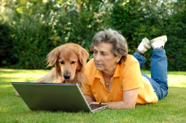 senior with dog on a laptop