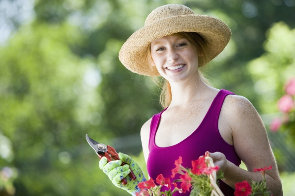 smiling young woman cutting flowers