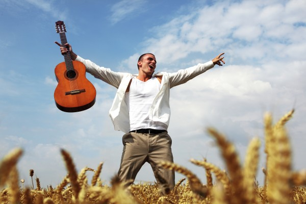 young man with guitar in corn