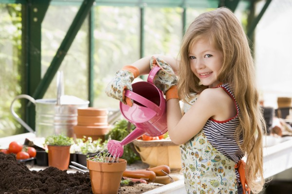 young girl in greenhouse watering potted