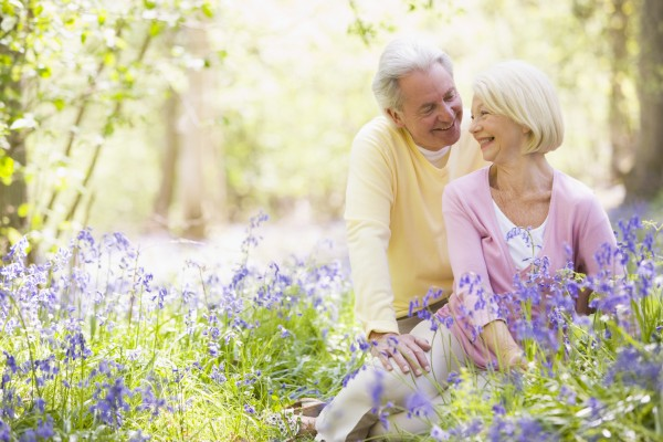 couple sitting outdoors with flowers smiling