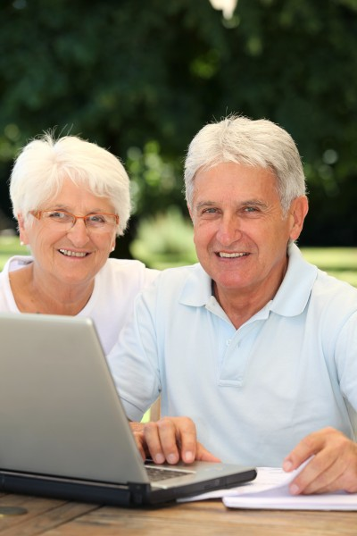 senior couple at home surfing on