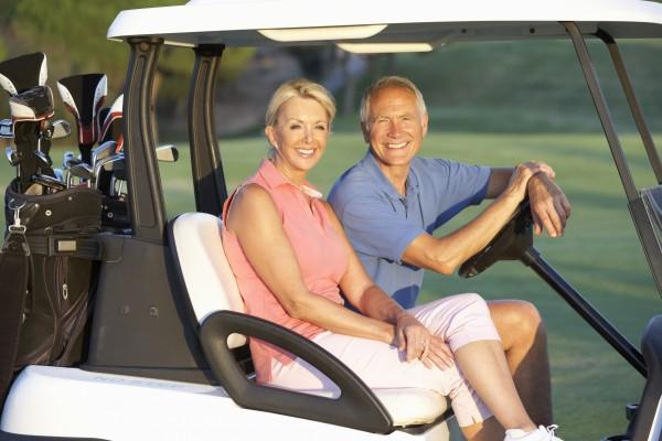 senior couple riding in golf buggy