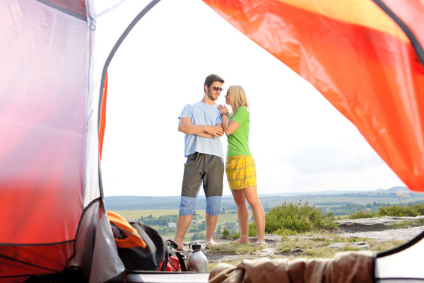 camping young couple outside tent panoramic