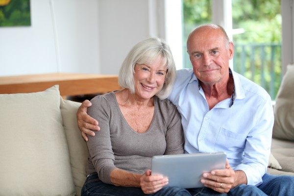 senior couple using electronic tablet at