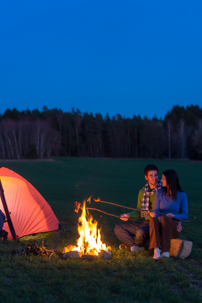 camping night couple cook by campfire