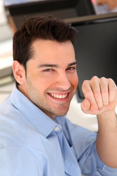 smiling trader in front of desktop