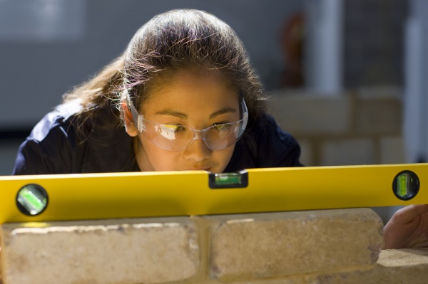 bricklaying student using level on brick