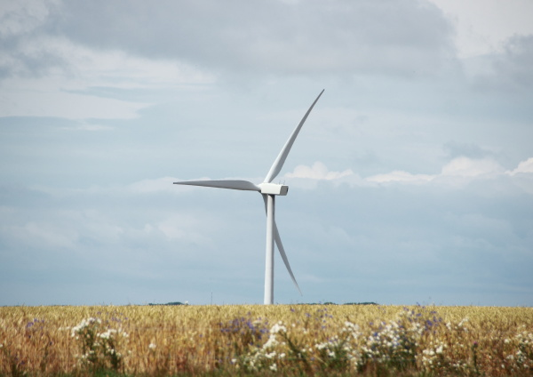 single windmill in grass field with