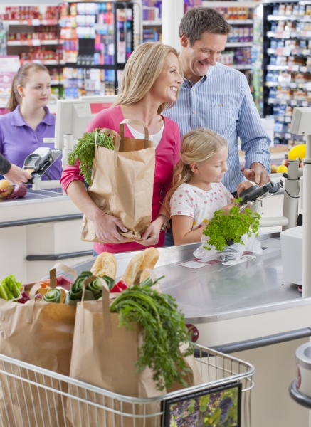 family paying for shopping at supermarket