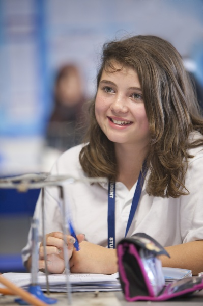 smiling girl experimenting with bunsen burner