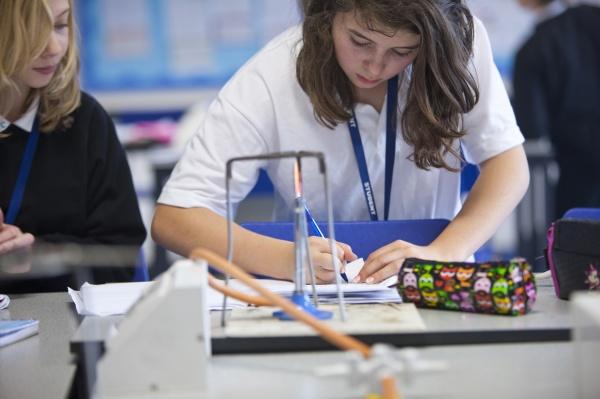 girls taking notes near bunsen burner