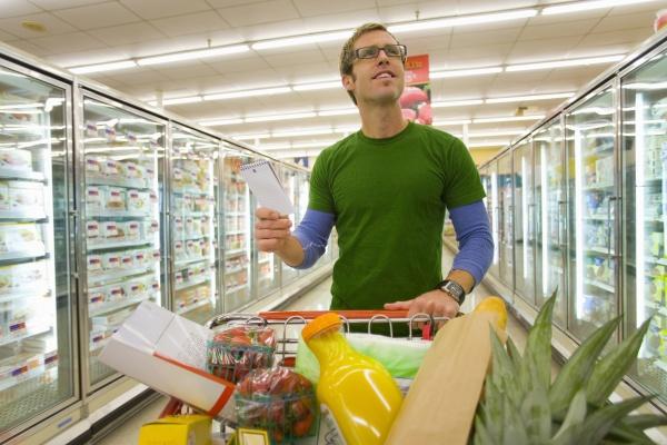 man grocery shopping in frozen foods