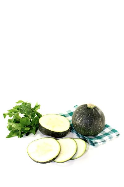 round raw zucchini on a green