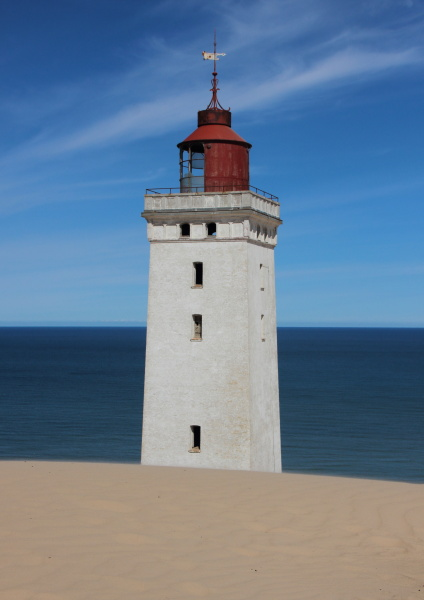lighthouse with sand dune and blue