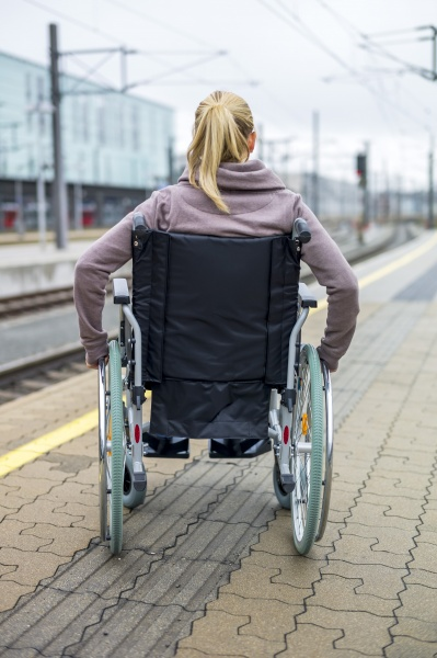woman in wheelchair waiting at station