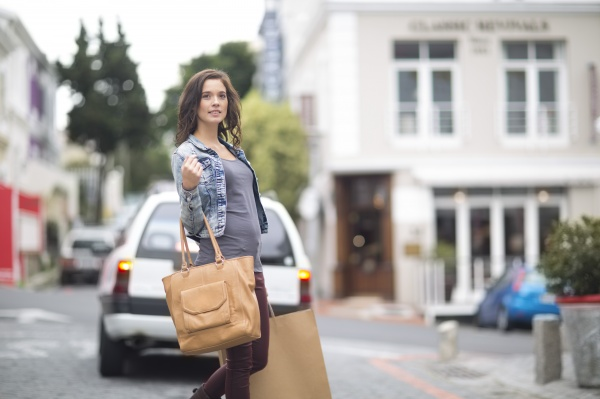 woman with shopping bag walking on