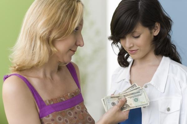 mother giving teenage daughter pocket money
