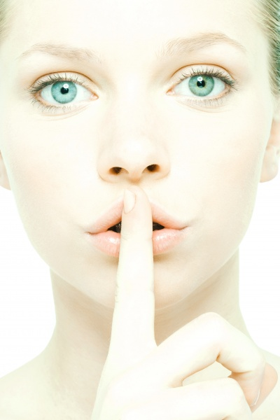 teenage girl holding finger over lips