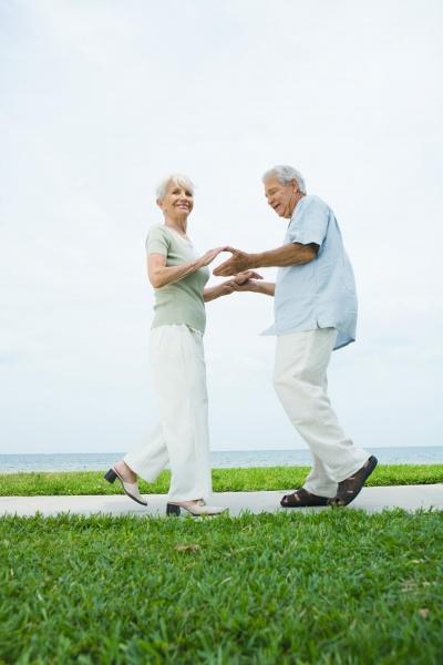 senior couple dancing on sidewalk overlooking