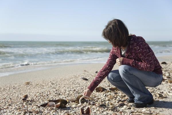 woman collecting seashells at the beach