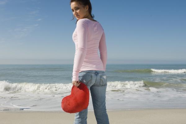 preteen girl at beach holding stuffed