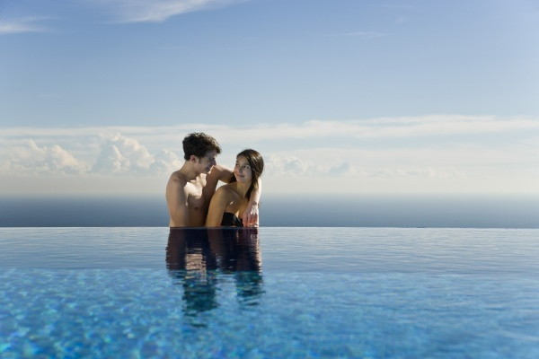 couple relaxing together next to infinity