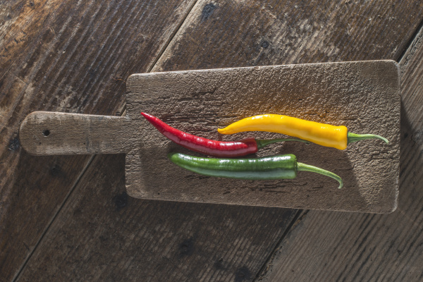 three chili peppers on old wooden