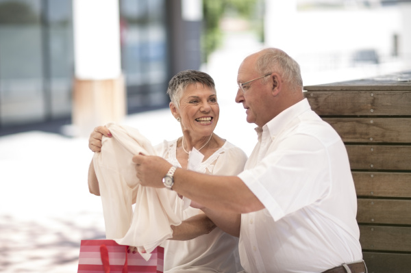 senior woman showing husband purchase