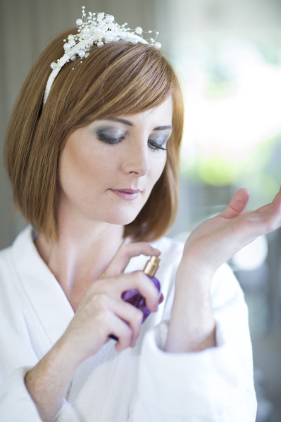 young woman applying fragrance
