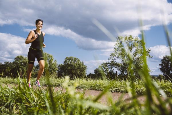 female triathlete running on dirt track