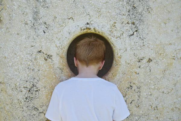 boy peeking through hole in wall