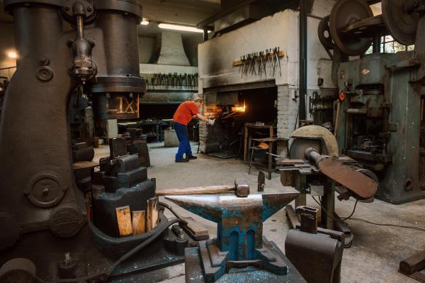 senior blacksmith working in hammer mill