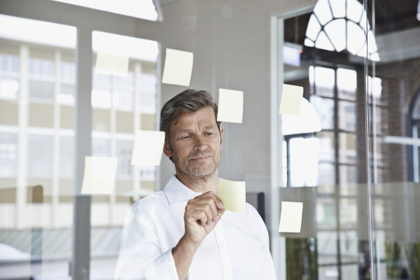 businessman with sticky notes on glass