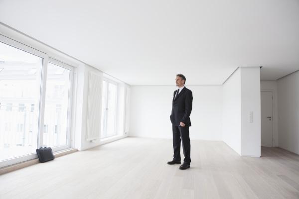 estate agent standing in empty apartement
