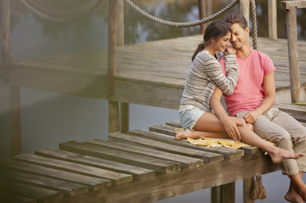 affectionate couple sitting on dock over
