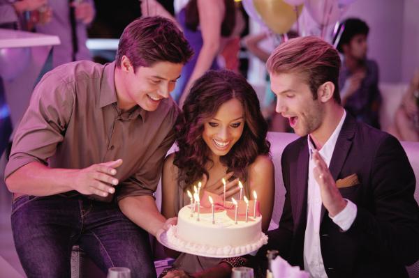 friends with birthday cake in nightclub