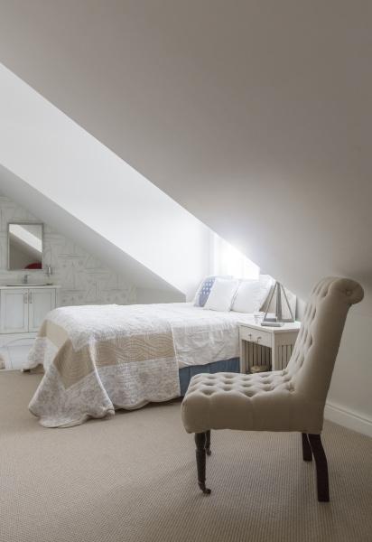 bed under window in attic bedroom