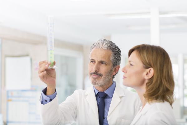 scientists examining green liquid in tube