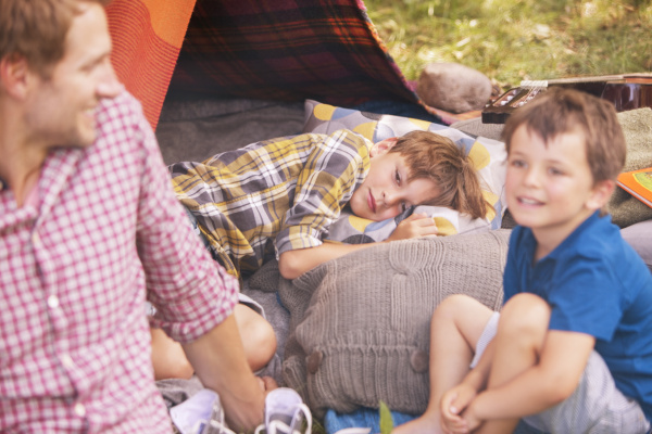 father and sons smiling at camping