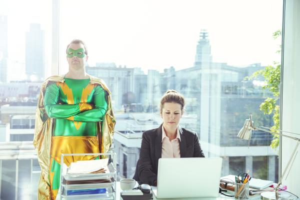 superhero standing near businesswoman working in