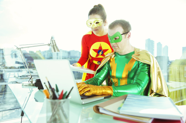superheroes working with laptop in office