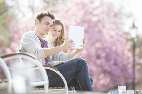 couple using digital tablet in park