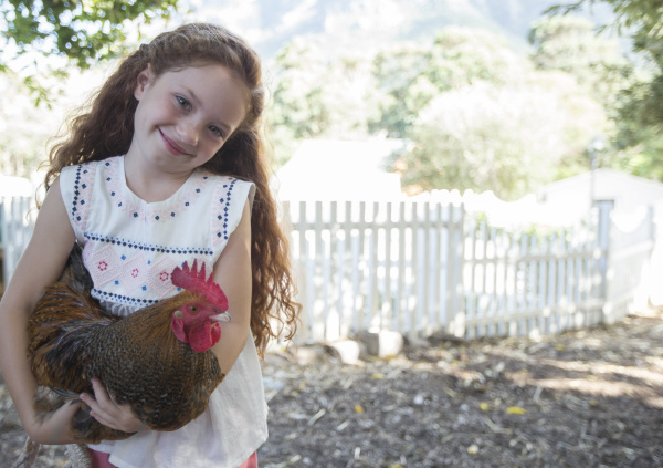 girl holding chicken at petting zoo