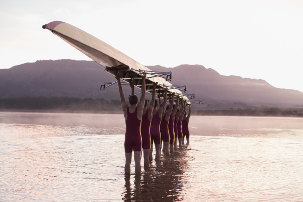 rowing team carrying row boat overhead